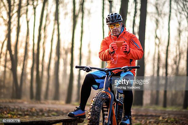 Cyclist holding mobile phone in the forest