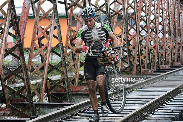 A cyclist holds his bike to cross a railroad bridge during the last stage of the Route of Conquerors mountain bike race 17 November 2007 in Playa...