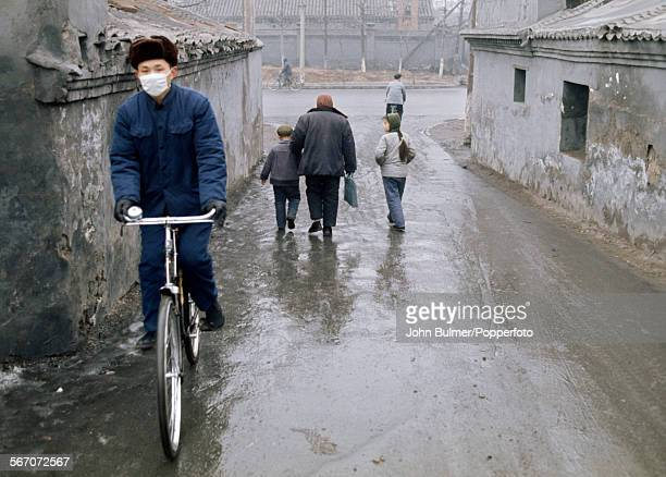 A cyclist in a backstreet in Beijing China during the Cultural Revolution 1973