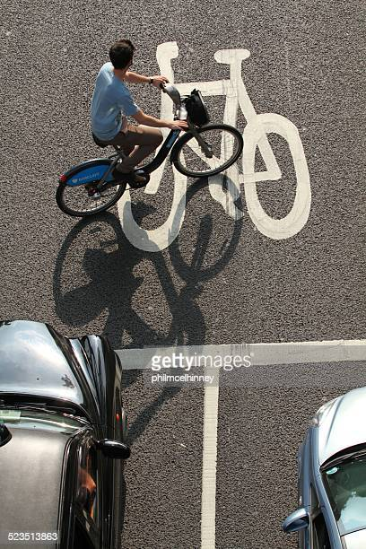 cyclist in a cycle lane. - barclays cycle hire stock pictures, royalty-free photos & images