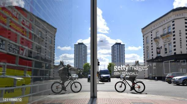 A cyclist in a face mask is reflected in the window of a closed shop in the London borough of Newham east London on May 2 as life in Britain...