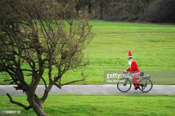 Cyclist in a Santa Claus costume cycles through Alexandra Park outside the venue prior to Day Two of the 2020 William Hill World Darts Championship...
