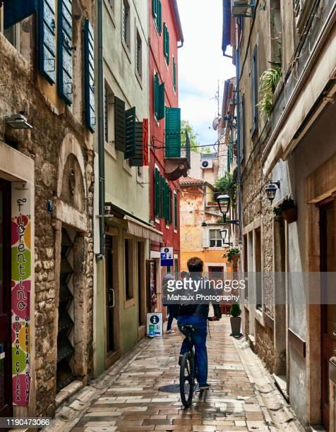 a cyclist in a typical alley of the old town of zadar. - limestone pavement stock pictures, royalty-free photos & images
