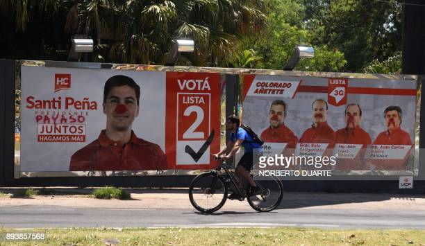 A cyclist in Asuncion on December 16 2017 passes by a vandalized billboard will electoral propaganda of Santiago Pena one of the ruling party's...