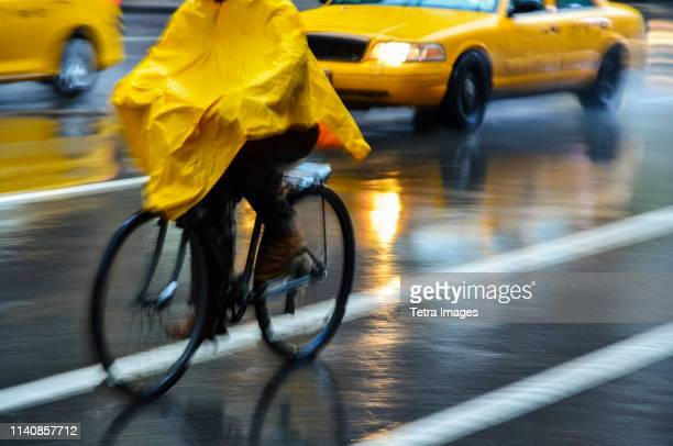 cyclist in yellow poncho during rain in new york city, usa - poncho stock pictures, royalty-free photos & images