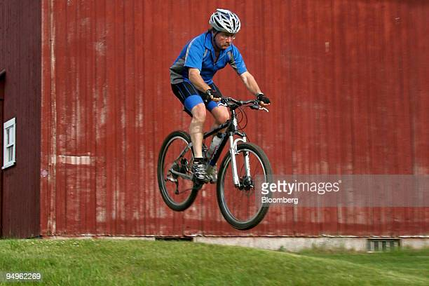 A cyclist is airborne while riding past a barn on the Kingdom Trails in East Burke Vermont US on Wednesday June 17 2009 Kingdom Trails features 100...