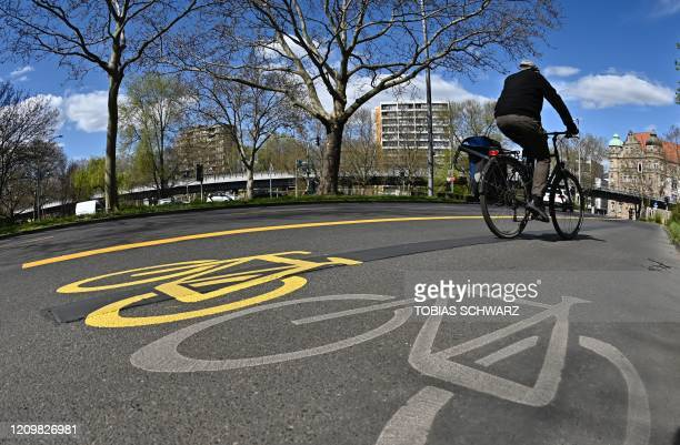 A cyclist is pictured on an expanded cycling track in a street in Berlins Kreuzberg district on on April 14 amid the new coronavirus / COVID19...