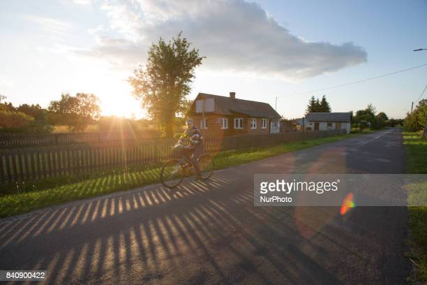 Cyclist is seen in a small village near the Bialowieza nature area on 18 July, 2017.