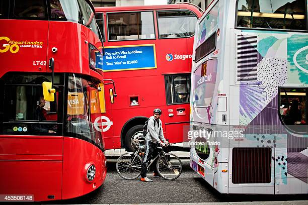 A cyclist is stuck between three buses in Central London