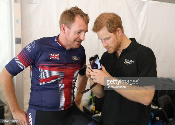 Cyclist Jamie Weller of Great Britain shows Prince Harry voice activation technology at the Cycling Time Trial during the Invictus Games 2017 at High...