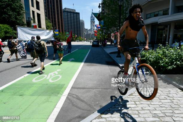 A cyclist jump while passing a protest march trough Center City in Philadelphia PA on June 30 2018 Thousands participate in a rally earlier to...
