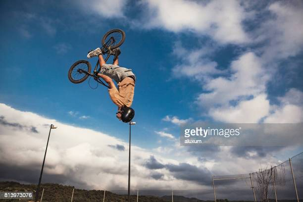 bmx cyclist jumping doing backflip. real jump - bmx cycling stock pictures, royalty-free photos & images