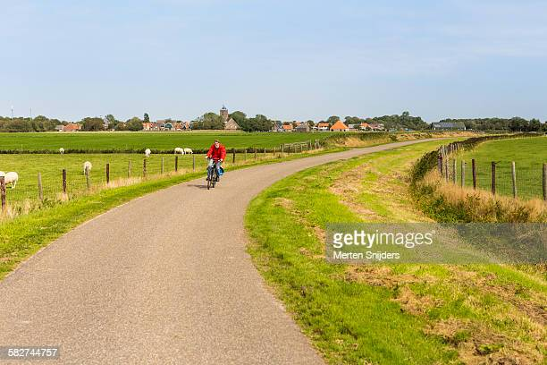 Cyclist leaving village into countryside