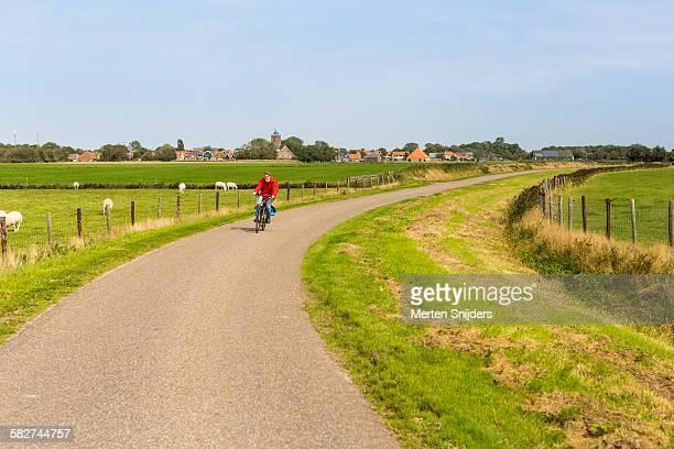 cyclist leaving village into countryside - friesland noord holland stockfoto's en -beelden