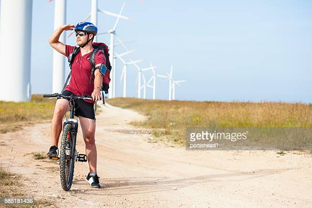 Cyclist looking for direction in front of wind turbine farm