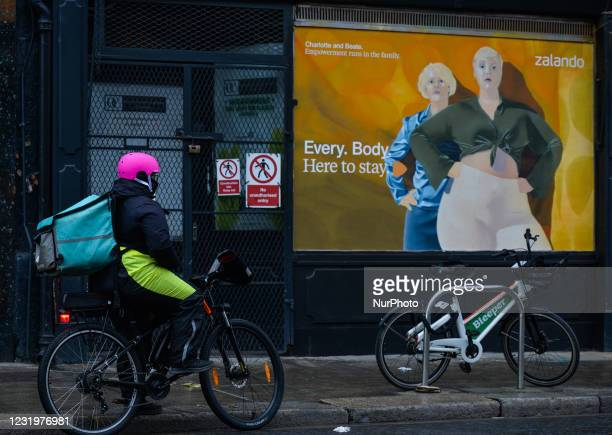 Cyclist looks at a new mural by Irish artists Cormac Dillon and Loughlin Brady Smith in Dublin city center. The Zalandos spring marketing campaign...