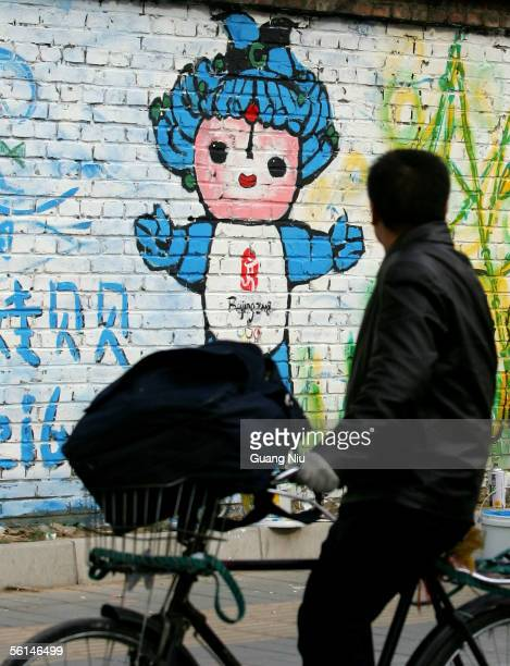 A cyclist looks at graffito of the Beijing 2008 Olympic mascots on the wall November 12 2005 in Beijing China Beijing Olympic organizers chose five...