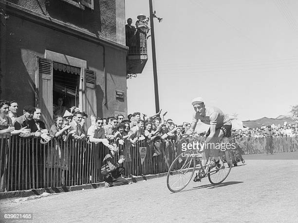 Cyclist Louison Bobet is cheered by the crowd during the 20th stage of the 1953 Tour de France. | Location: Between Lyons and St.-Etienne, France.