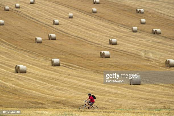 A cyclist makes his way through a farmers field past hay bales on August 15 2018 in Cudham England The National Farmers' Union has warned that...