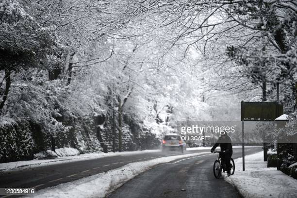 Cyclist makes their way along a snow covered road in Marsden, northern England on January 14, 2021 as heavy snow fell on parts of the UK. - A yellow...