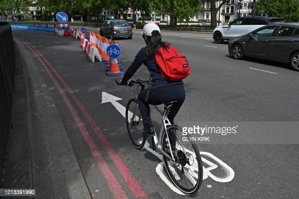 Cyclist makes use of a new expanded cycle lane on Park Lane in London on May 17 following an easing of lockdown rules in England during the novel...