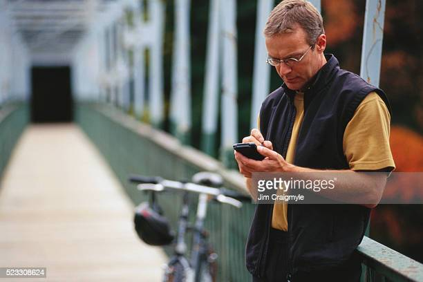 cyclist making digital notes - jim craigmyle stock pictures, royalty-free photos & images