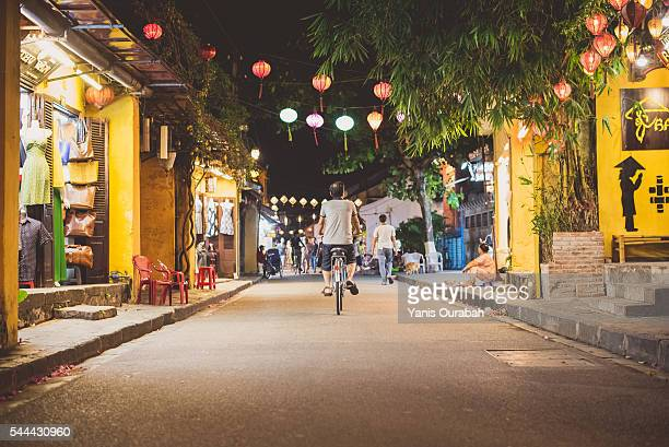 Cyclist male in Hoi An traditional street by night in summer with lanterns