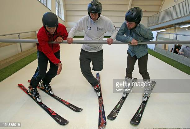 Cyclist Mark Cavendish watches as skier Graham Bell shows amputee Andy Barlow how to ski on the new Skiplex slope that has been installed at the new...