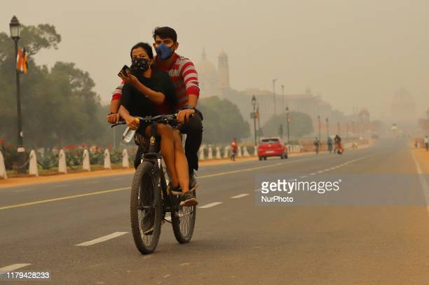 Cyclist moves on the Rajpath on a smoggy morning in New Delhi India on 02 November 2019
