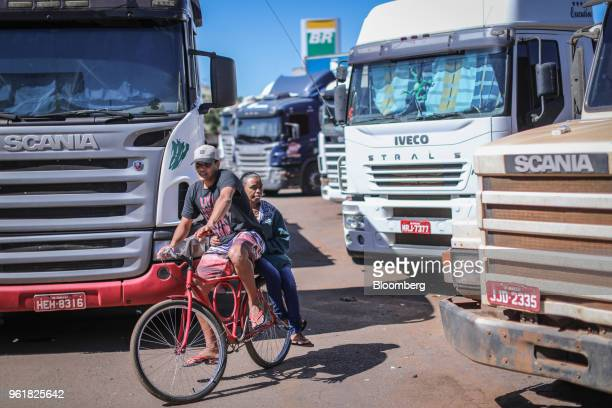 A cyclist navigates around parked trucks on BR 040 highway during a protest against rising fuel prices in Luziania Brazil on Wednesday May 23 2018...