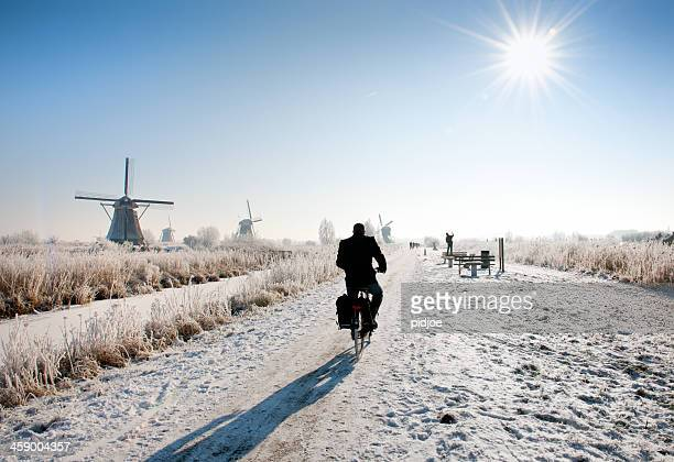 cyclist near windmills at Kinderdijk in wintry landscape