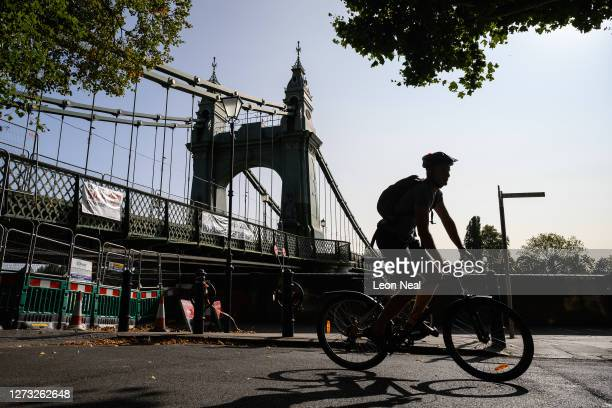 Cyclist negotiates the closed pathways around Hammersmith Bridge which has now been closed for nearly a year and a half due to safety concerns, on...