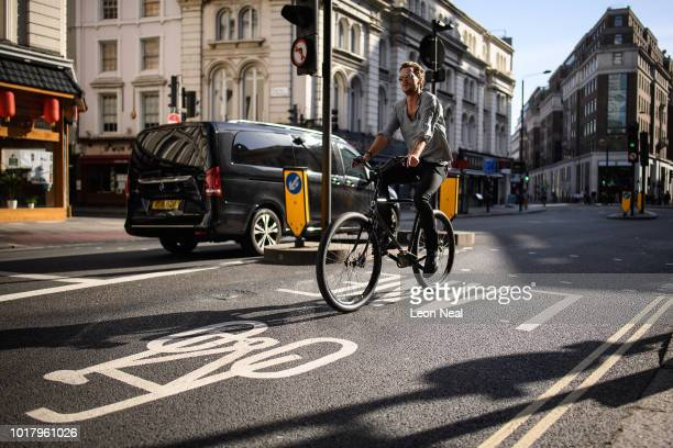 A woman takes a photograph of an abandoned bicycle on August 17 2018 in London England Dr Peter Fisher one of three official Physicians to The Queen...