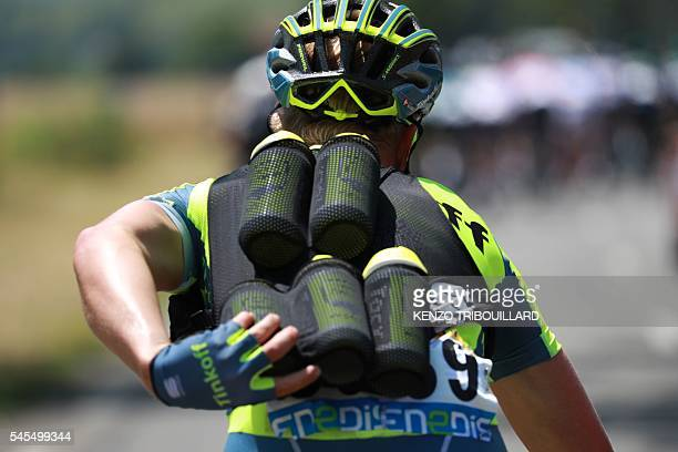 A cyclist of Russia's Tinkoff cycling team carrying feeding bottles for his teammates rides during a sunny day as part of the 1625 km seventh stage...