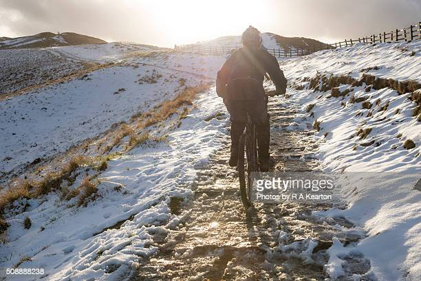 Cyclist on an icy path to Mam Tor in the Peak District