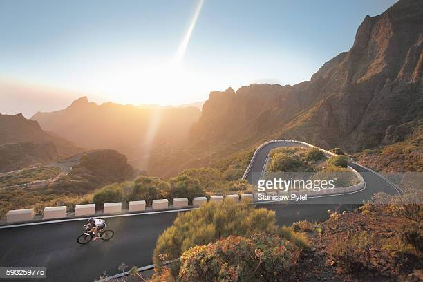 cyclist on beautiful road in mountains at sunset - isla de tenerife fotografías e imágenes de stock
