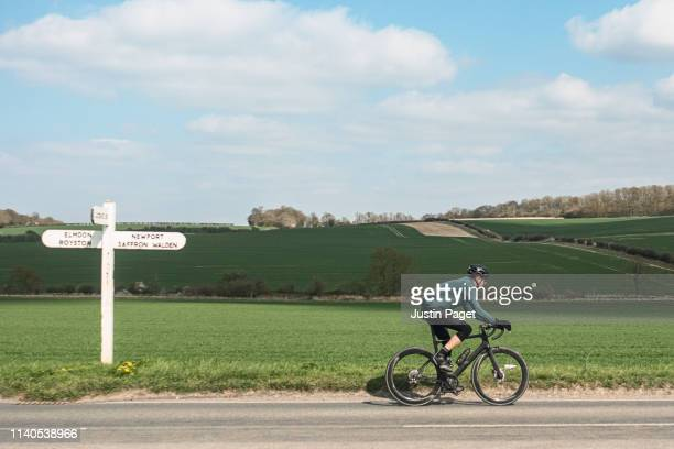 cyclist on country road - cycling stock pictures, royalty-free photos & images