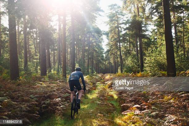 cyclist on forest path - headwear stock pictures, royalty-free photos & images