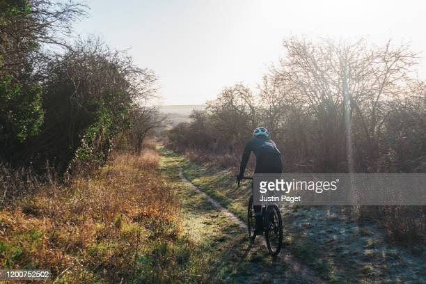 cyclist on frost countryside path - riding stock pictures, royalty-free photos & images