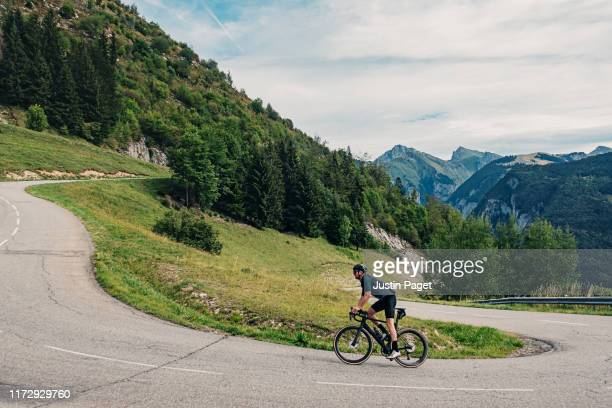 cyclist on hairpin bend on col de corbier - mountain pass stock pictures, royalty-free photos & images