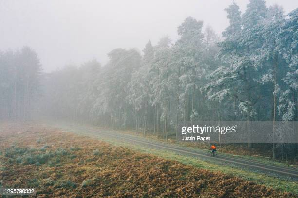 cyclist on misty forest track - drone point of view stock pictures, royalty-free photos & images
