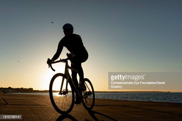 cyclist on path by sea at sunset - cycling stock pictures, royalty-free photos & images