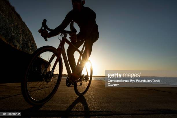 cyclist on path by sea at sunset - males stock pictures, royalty-free photos & images