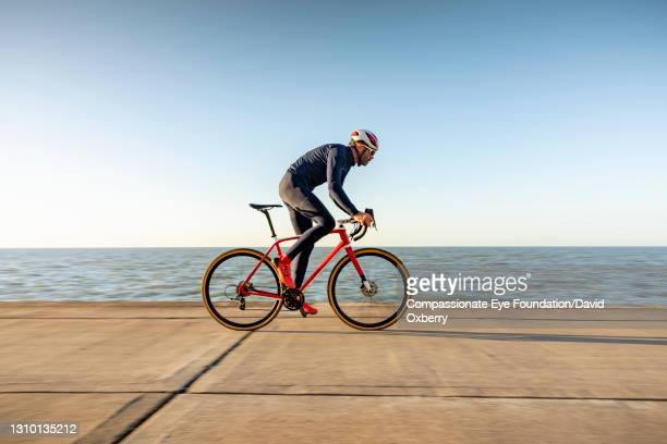 cyclist on path by sea - riding stock pictures, royalty-free photos & images