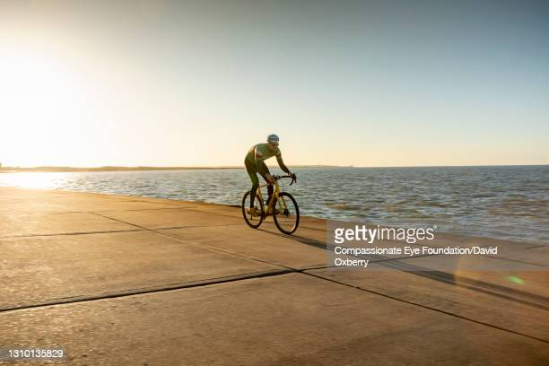 cyclist on path by sea - horizon stock pictures, royalty-free photos & images