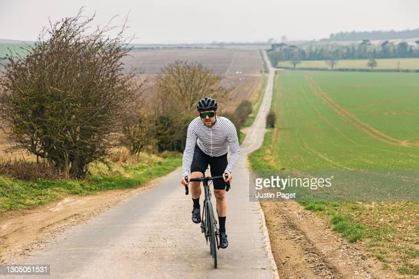cyclist on road in countryside - riding stock pictures, royalty-free photos & images