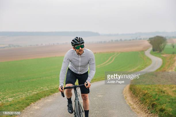 cyclist on road in countryside - printed sleeve stock pictures, royalty-free photos & images