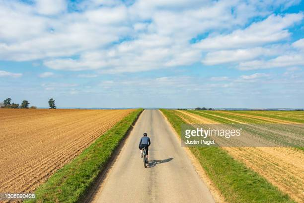 cyclist on road in countryside - landscape scenery stock pictures, royalty-free photos & images