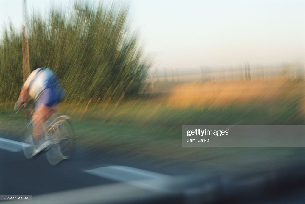 Cyclist on road, rear view (blurred motion) : Stock Photo