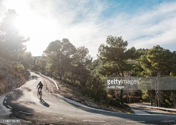 cyclist on steep hairpin - wielrennen stockfoto's en -beelden